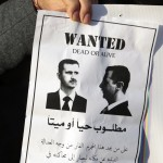 An anti-Syrian regime protester holds a paper showing President Bashar Assad at a sit-in held by Lebanese media advocates in Beirut, Lebanon, on Friday.