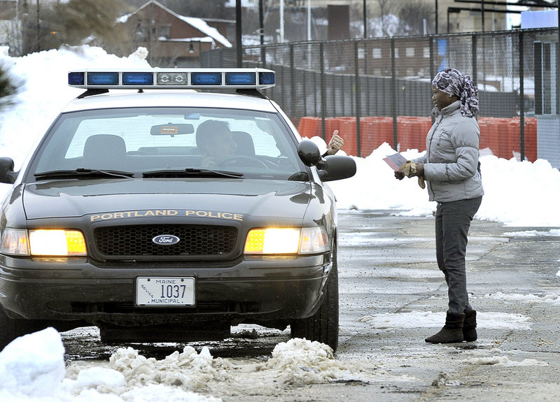 Marwa Abdalla of Portland shows a Portland police officer proof of payment to get her car out of impoundment at the Maine State Pier lot Friday after it was towed Thursday night during Portland's parking ban.