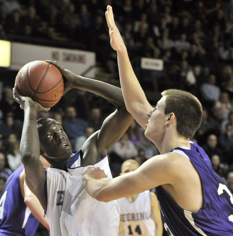 Deering's Labson Abwoch looks to get a shot off over Hampden's Logan Poirier in Saturday's Class A title game. It was the third time the teams had met in the state final.