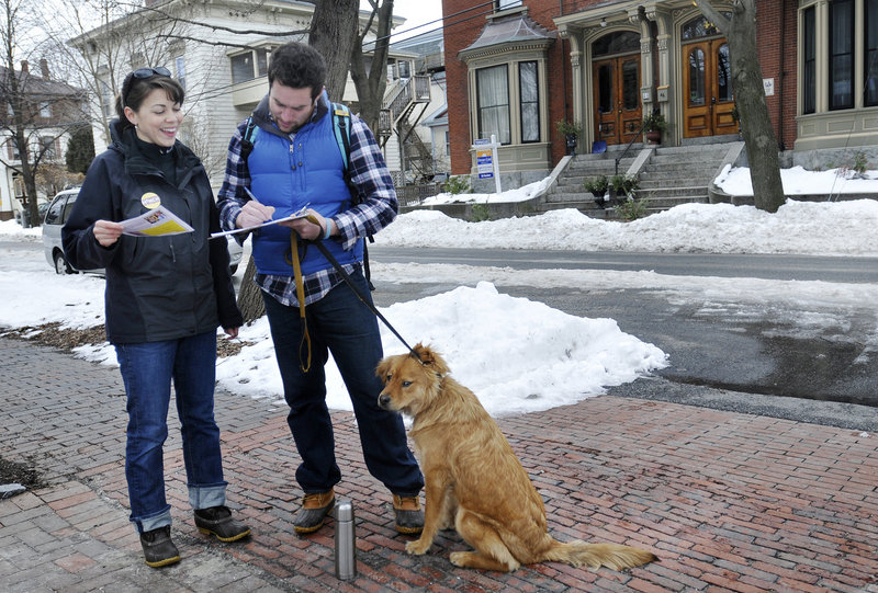 Stephanie O'Brien of Portland collects signatures to get Democrat Jon Hinck on the ballot as a candidate for the 1st District congressional seat. Signing is Justin Moss of Portland. O'Brien was going door to door on Carleton Street in Portland on Sunday.