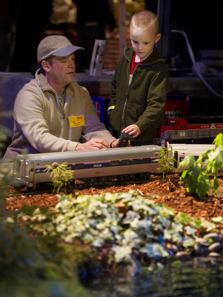 Chris Paquette of Robin's Nest Swimming Environments shows 6-year-old Jackson Fischer of Lisbon Falls how to operate a model train on Paquette's display during the opening of the Portland Flower Show on Wednesday.