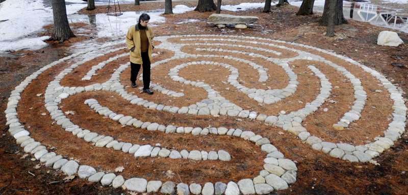 "Deirdre McClure of Portland follows the path of a recently completed labyrinth at the University of New England's Portland campus during an opening reception for the project Thursday. Intended as a meditative tool, the labyrinth, located behind the art gallery, was created by landscape architect Ethan Stebbins. ""Walking the labyrinth can provide healing properties,"" according to Cali Johnson, coordinator of UNE Counseling Services."