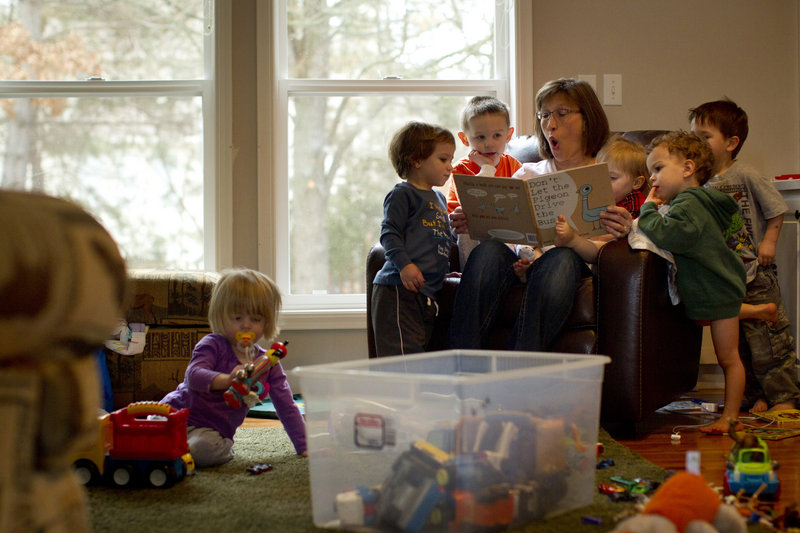 Denise Sjoberg reads books to children last month at the day care she runs at her home in Eagan, Minn. Laid off last year from her job negotiating IT contracts, Sjoberg couldn't find a new job in her field and decided to open her own business.