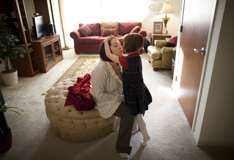 Kate Madonna Hindes hugs her daughter, Ava, before starting her new job in Chaska, Minn., in February.