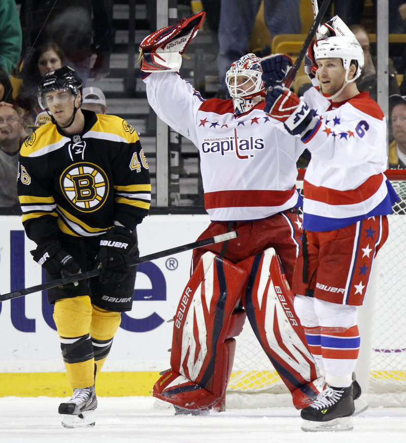 Capitals goalie Tomas Vokoun and defenseman Dennis Wideman celebrate a 4-3 win at Boston Saturday as Bruins forward David Krejci shows his disappointment.