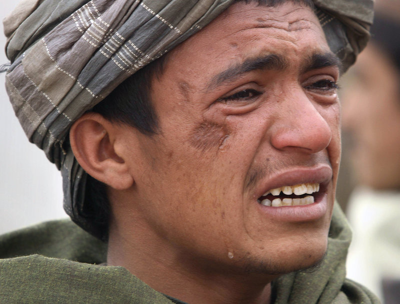 An Afghan youth mourns for relatives who were allegedly killed by a U.S. service member in Panjwai, Kandahar province, Afghanistan, on Sunday.