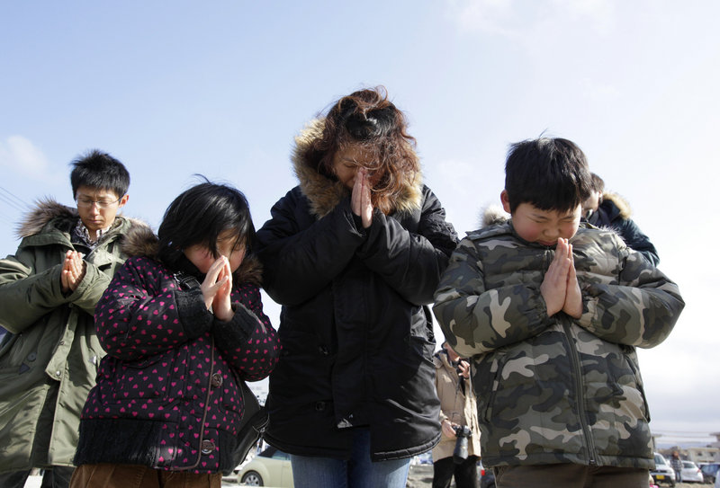 A Japanese family observes a moment of silence in front of what is left of a disaster control center in an area devastated by the March 11, 2011 earthquake and tsunami in Minamisanriku, Japan, on Sunday.
