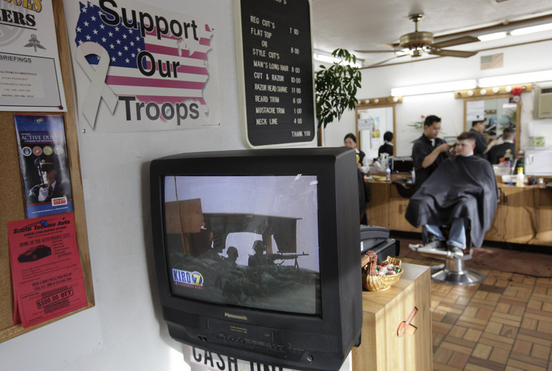 Army Spc. Jared Richardson, right, of Salt Lake City gets his hair cut Sunday as he watches television news in Lakewood, Wash., near Joint Base Lewis-McChord. An Army sergeant from the base allegedly opened fire Sunday on villagers in Afghanistan as they slept, killing 16 people in an attack that reignited fury at the U.S. presence.
