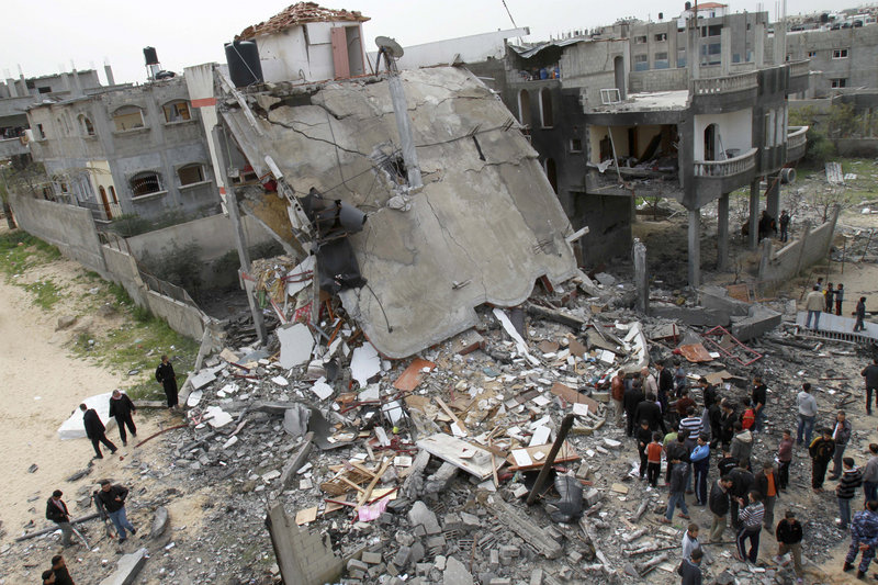 "Palestinians inspect the rubble of a building after an Israeli airstrike in Jabaliya on Monday. Prime Minister Benjamin Netanyahu warned Israel is ""ready to broaden its operation."""