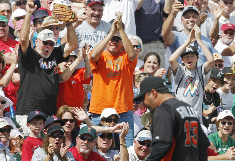 Ozzie Guillen, the new manager of the Miami Marlins, draws a reaction from fans Monday in Fort Myers, Fla., after being ejected for arguing a foul-ball call during Boston's 5-3 victory in 10 innings.