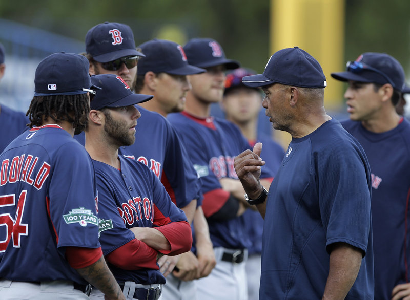 Dustin Pedroia, the Red Sox second baseman, talks with Hall of Famer Reggie Jackson prior to Boston's spring training game with the New York Yankees on Tuesday. The Red Sox won, 1-0.