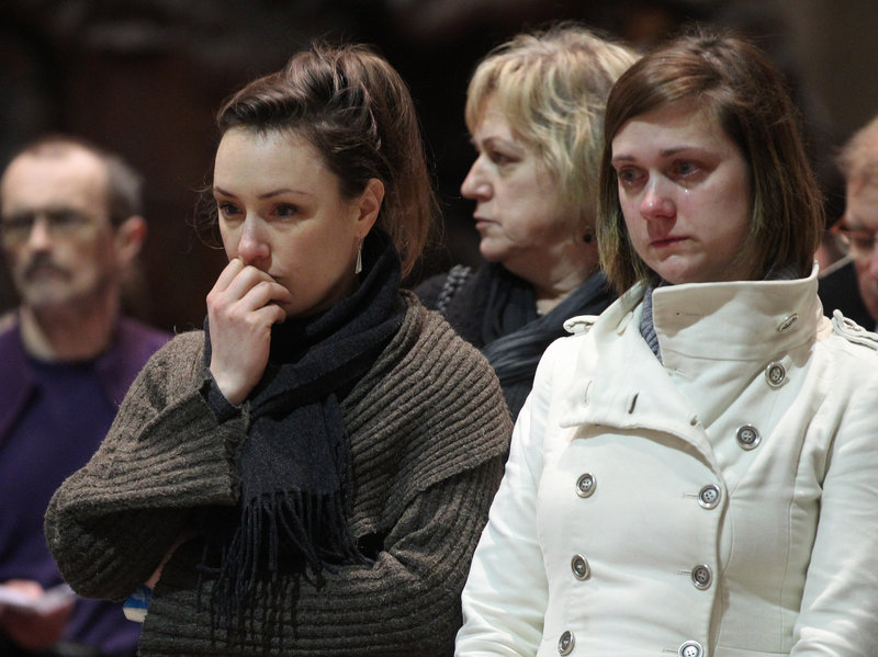 Two teachers from the Sint Lambertus school in Heverlee attend a mass at the Saint-Peters church in Leuven, Belgium, Wednesday, held for the bus crash victims.