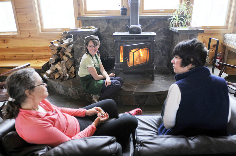 Linda Laird, left, and Kathleen Fetissoff, both of New Jersey, relax by the fire in the Flagstaff Lake Hut. Jenny Baxter, a crew member, stocks the wood stove.