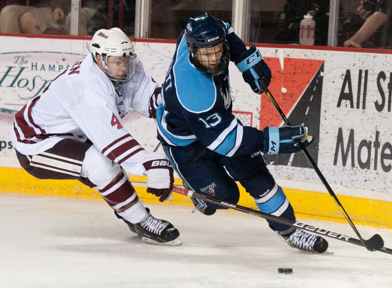 Maine forward Spencer Abbott takes the puck behind the net while defended by Massachusetts' Conor Allen in a November hockey game in Amherst, Mass. Abbott suffered an apparent concussion during the Hockey East semifinals last weekend in Boston.
