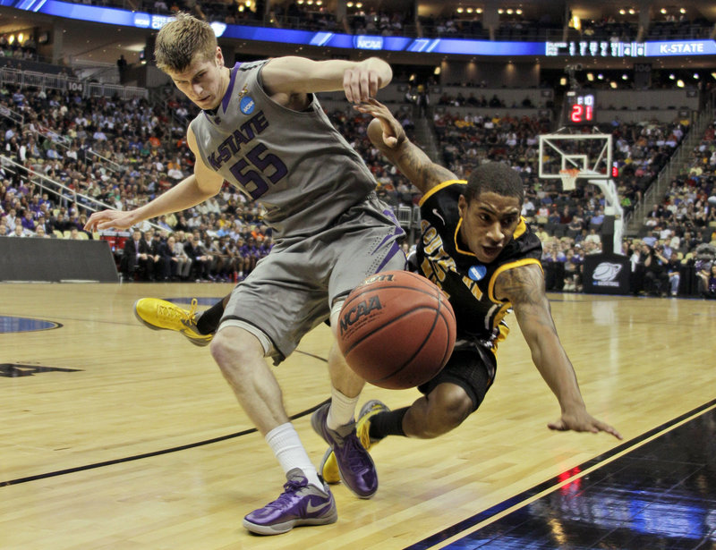 The ball heads out of bounds Thursday as Will Spradling of Kansas State, left, collides with Neil Watson of Southern Mississippi during Kansas State's 70-64 victory in the first round of the NCAA tournament.