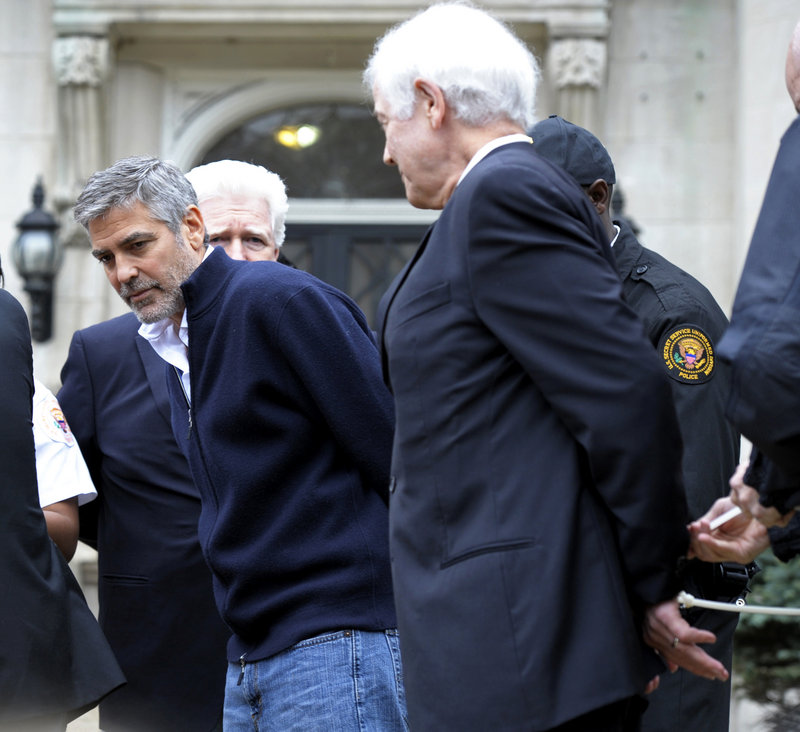 Actor George Clooney, center, Rep. Jim Moran, D-Va., back, and Clooney's father, Nick Clooney, right, are arrested during a protest at the Sudanese Embassy in Washington on Friday. Earlier, Clooney spoke out against the violence in Sudan.