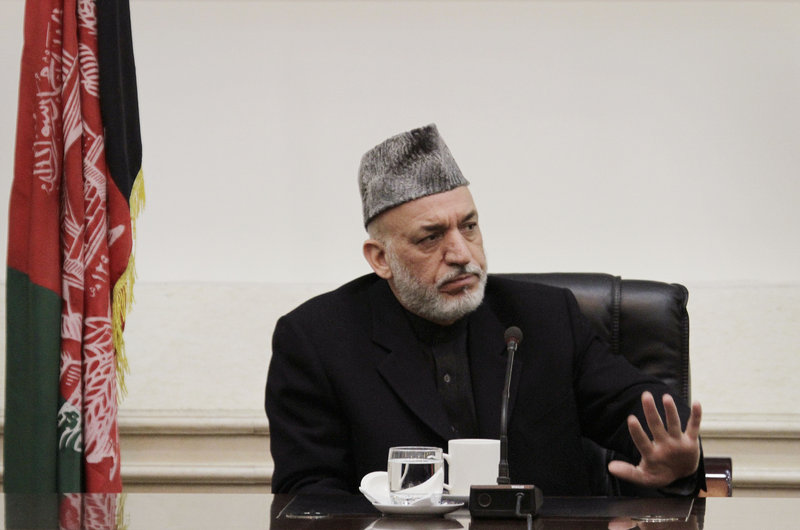 Afghan President Hamid Karzai listens to family members of last Sunday's massacre.