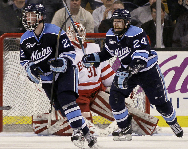 Stu Higgins, left, and Mark Anthoine of the University of Maine celebrate a goal by teammate Will O'Neill as Boston University goaltender Kieran Millan reacts in the second period Friday night. The Black Bears won, 5-3.