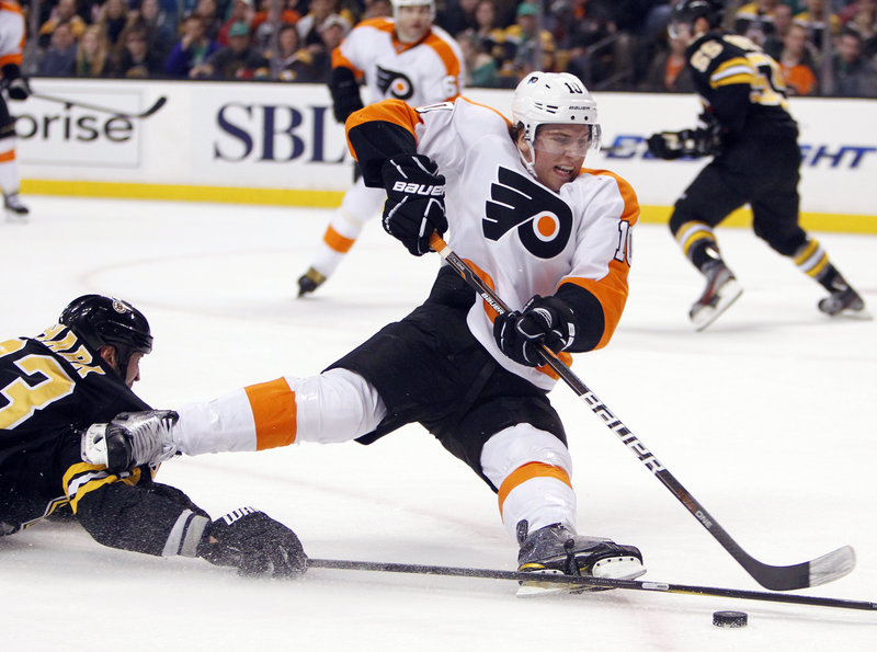 Brayden Schenn of the Flyers gets tripped up by Boston's Zdeno Chara in Saturday's game at Boston. The Bruins blew a 2-0 goal lead but came back to win 3-2 in a shootout, halting a four-game skid.