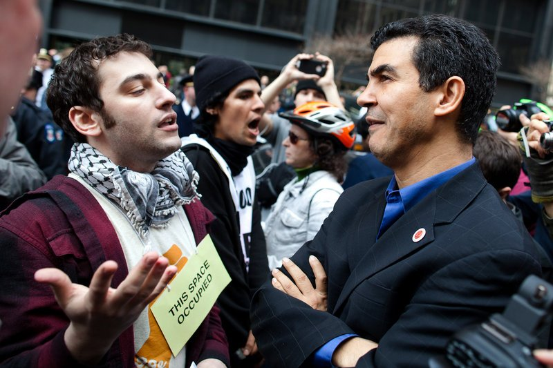 New York City Councilman Ydanis Rodriguez listens to an Occupy Wall Street demonstrator in Zuccotti Park after a march to celebrate the protest's sixth month Saturday. A couple hundred people attended.
