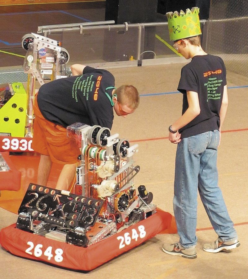 Infinite Loop Robotics Team members Ian Bernier, left, and Bradley Bickford handle their competition robot during a recent robotics event.