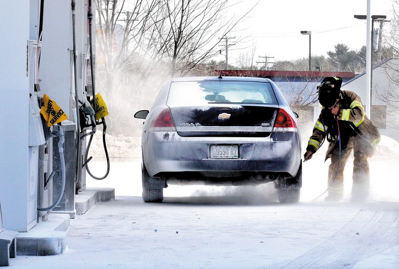 A firefighter responds to the Irving Circle K gas station on Route 201 in Skowhegan on Sunday, after a cloud of fire-suppression powder was emitted from about 50 hoses installed in the roof of the fuel-pumping area. The chemical covered vehicles, people and the station's parking lot.