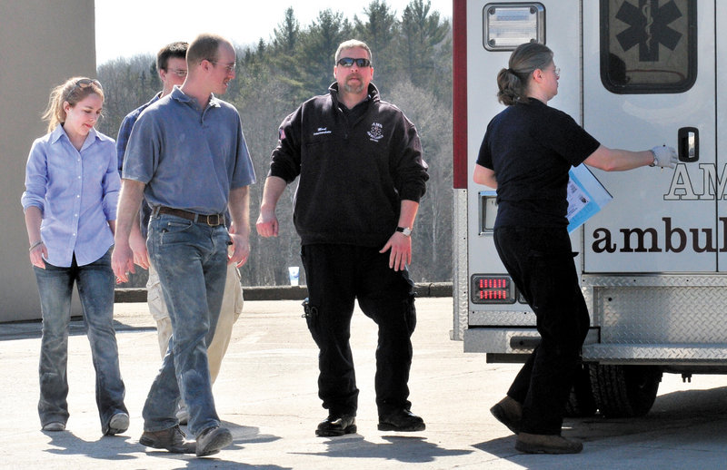 """Three people at left, including customer Becca Mattingly, are led to an ambulance to be examined after they were covered with a fire-suppressant powder that was released and covered people, vehicles and the road at the Irving Circle K store in Skowhegan on Sunday. """"I was shocked and scared at first but I'm all right,"""" Mattingly said later."""
