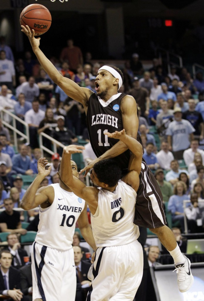 Mackey McKnight of Lehigh drives into Xavier's Dee Davis in Sunday's game at Greensboro, N.C. Xavier advanced, 70-58.