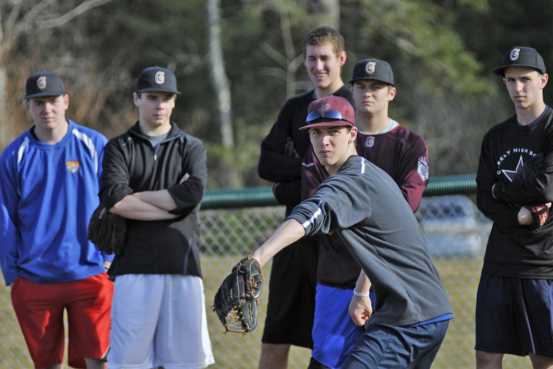 Will McAdoo of Greely works on a pickoff move as the pitchers look on during the Rangers' first practice of the season Monday at Cumberland. Due to the warm temperature, many teams were able to leave their gyms and work outside, a rare occurrence in Maine.