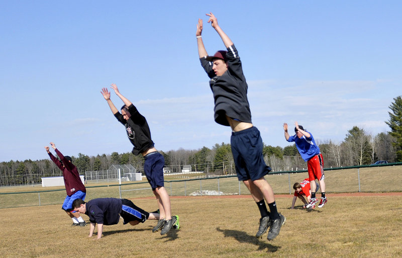 Greely High School baseball players exercise during their first practice Monday, the opening day for pitchers and catchers to prepare for the upcoming baseball season.