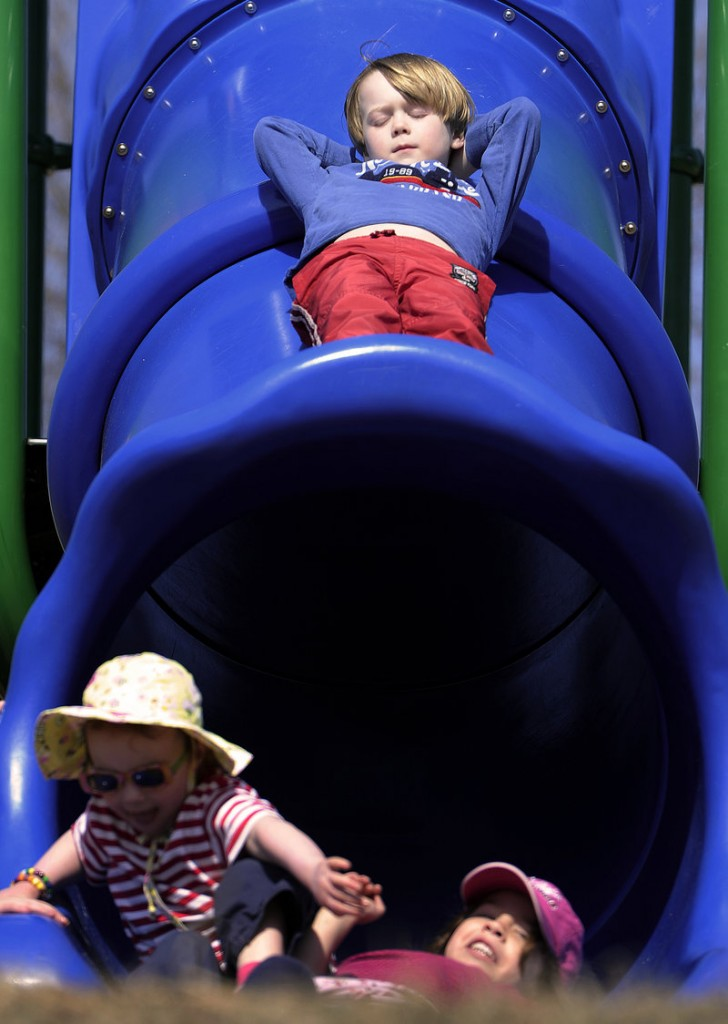 Ignoring the commotion beneath him, 6-year-old Oliver Moore of Yarmouth basks in the sun Tuesday on top of a slide at the North Road playground in Yarmouth on the first day of spring.