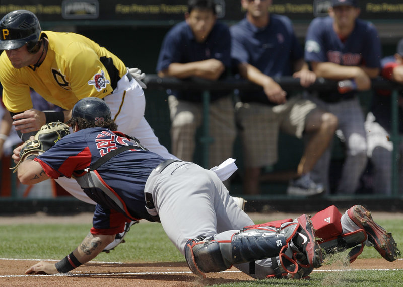 Red Sox catcher Jarrod Saltalamacchia lunges to tag out Matt Hague of the Pittsburgh Pirates, who was trying to score on a fielder's choice Wednesday. Pittsburgh won, 6-5.