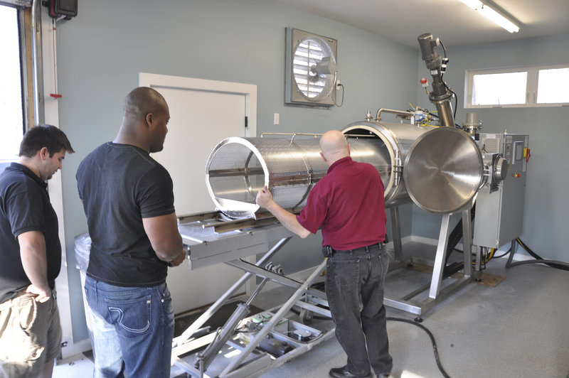 Jeff Edwards, right, explains to JoJo Oliphant, manager of Direct Cremation of Maine in Searsport, how to operate a cremation machine that uses a chemical process to dissolve a body in 12 hours.