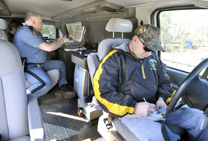 Maine State Police troopers Michael Cook and Steven Stubbs write up a ticket for a motorist using a cellphone and speeding as they patrol the Maine Turnpike in an unmarked van looking for drivers who are texting Thursday morning.