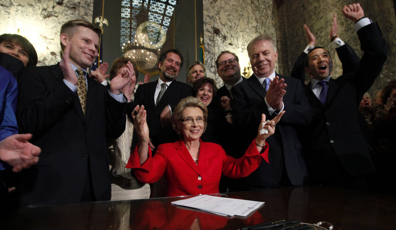 Washington state Gov. Christine Gregoire, seated, raises her arms as legislators and supporters cheer behind her after she signed into law a measure to legalize same-sex marriage.