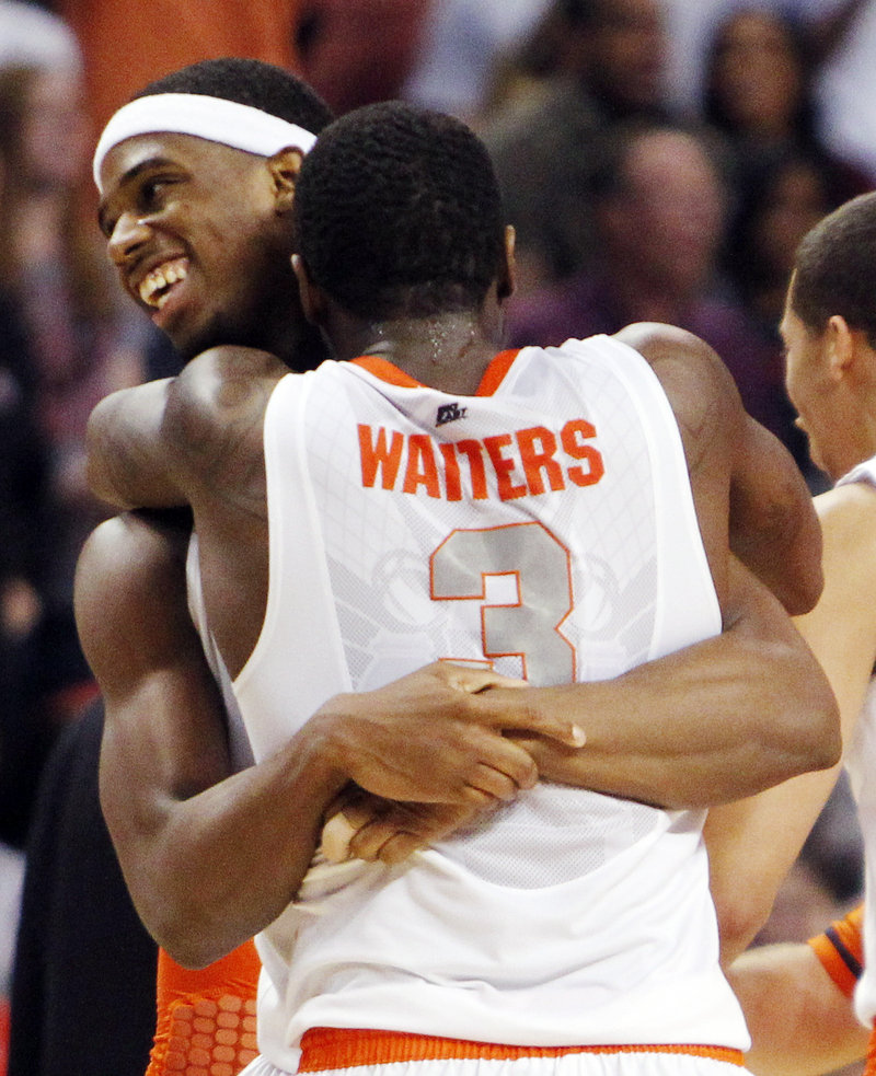 Dion Waiters and C.J. Fair embrace Thursday night after Syracuse moved within one victory of reaching the Final Four by holding on to a 64-63 victory against Wisconsin in the East Regional semifinals at Boston.