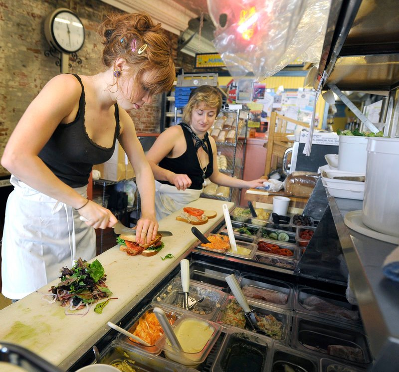 Rose Darrell and Sarah Smith make sandwiches at Big Sky Bakery in the Market House on Portland's Monument Square.