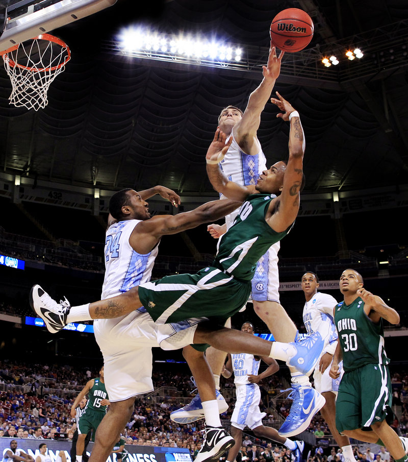 Tyler Zeller of North Carolina swats away a shot by D.J. Cooper of Ohio in the first half Friday night. The Tar Heels survived a serious challenge and came away with a 73-65 victory in overtime.