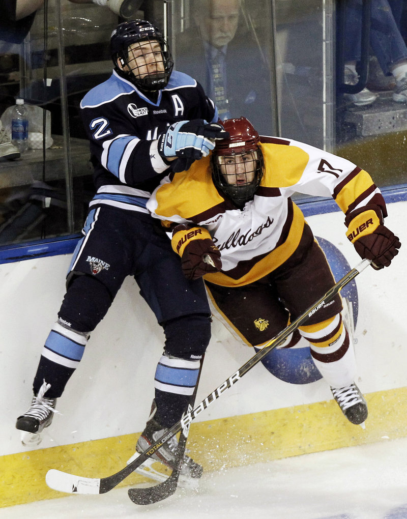 Mike Cornell of UMaine collides with Minnesota-Duluth's Mike Seidel during the second period Saturday night in Worcester, Mass. Minnesota-Duluth rallied for a 5-2 win to end UMaine's season.