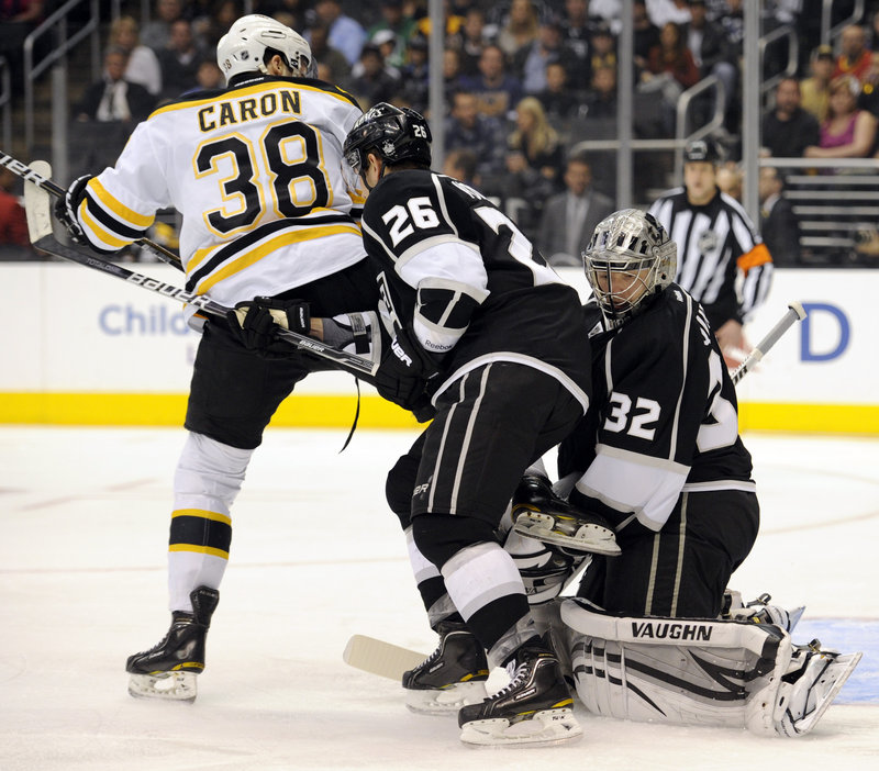 Jordan Caron of the Bruins positions himself in front of Kings goalie Jonathan Quick and defenseman Slava Voynov in Saturday's game at Los Angeles. The Bruins won, 4-2.