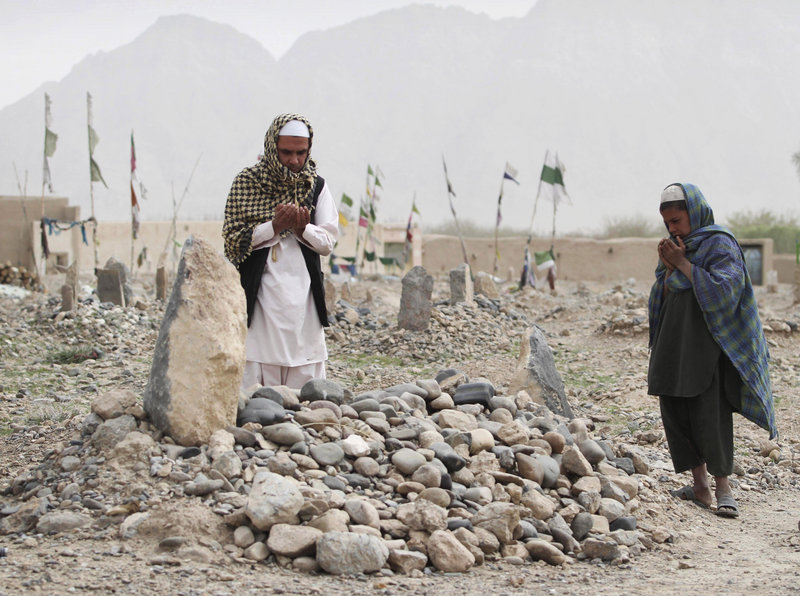 Afghanis pray over the grave of one of the shooting rampage victims on Saturday in the Panjwai district of Kandahar. Families of the dead have said seeing the killer punished is more important than financial compensation.