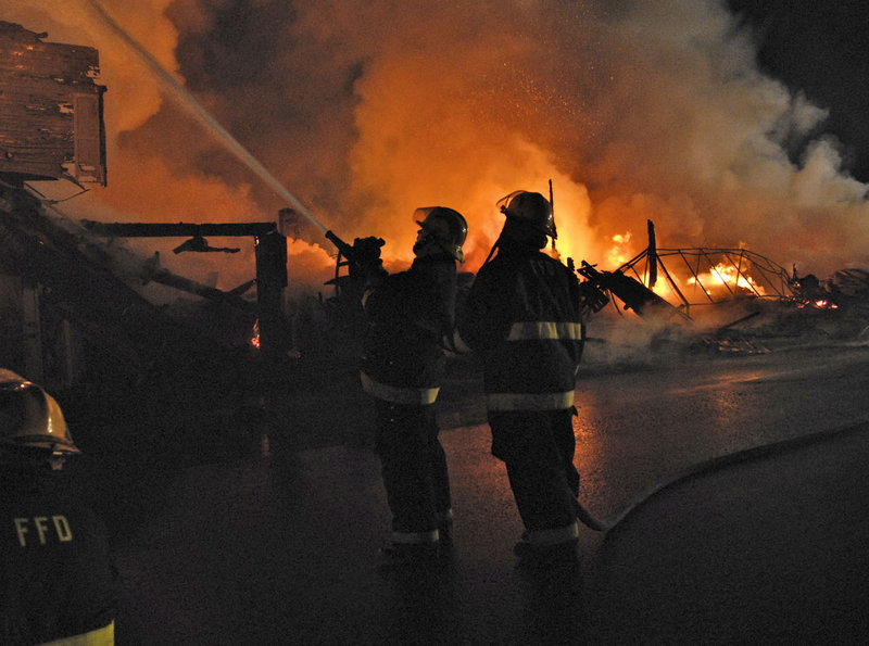 Firefighters work to put down a blaze that destroyed five buildings in downtown Fort Kent early Sunday. Nadeau's House of Furniture occupied three of the buildings, Acadia Home Care occupied a fourth, and the fifth was vacant.