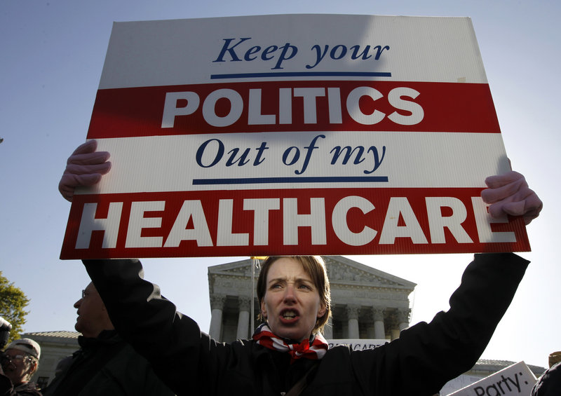 Amy Brighton of Medina, Ohio, shows her opposition to health care reform in front of the Supreme Court in Washington on Tuesday, as the court hears arguments on the Affordable Care Act, especially its individual insurance requirement.