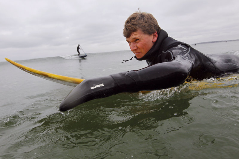 Joe Cormier of Westbrook paddles out to surf Thursday at Higgins Beach. Scientists say it's too soon to know all the effects of rising water temperatures in the Gulf of Maine.