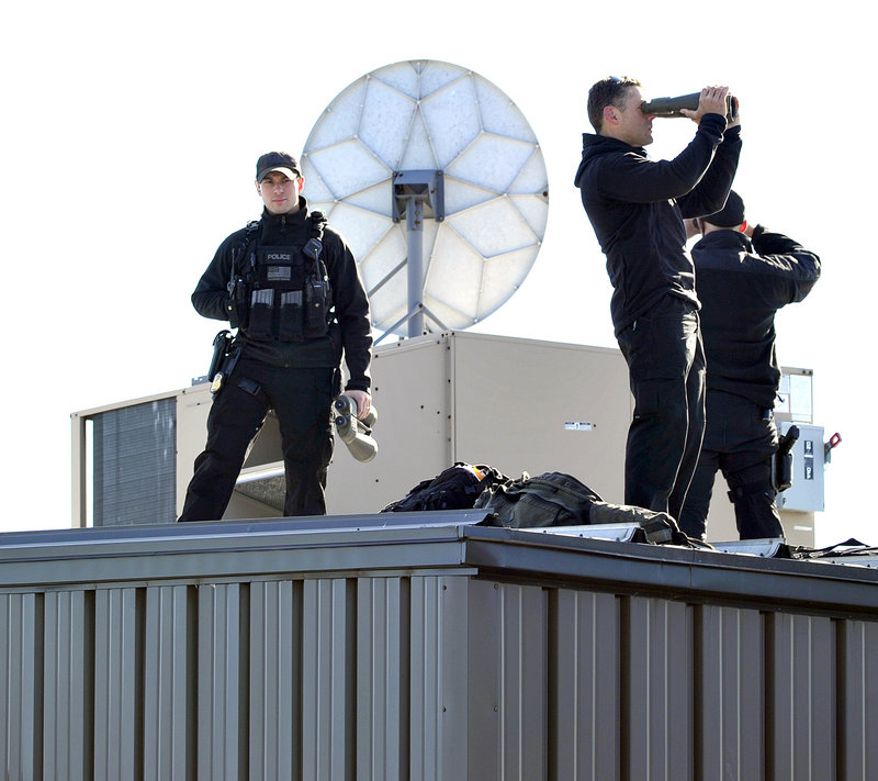 Sharpshooters scan the area from the rooftop as the president's plane lands at the Portland International Jetport.