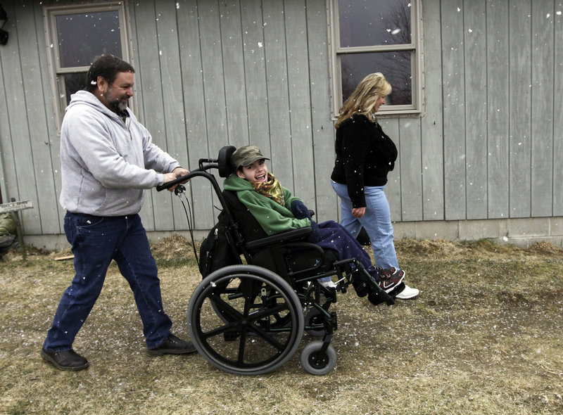 Ethan Kelly, 21, with his parents, Lisa and Alden Kelly, in Appleton on Wednesday. Planned cutbacks in the Department of Health and Human Services have raised concerns that the needs of people who can't care for themselves will not be met.