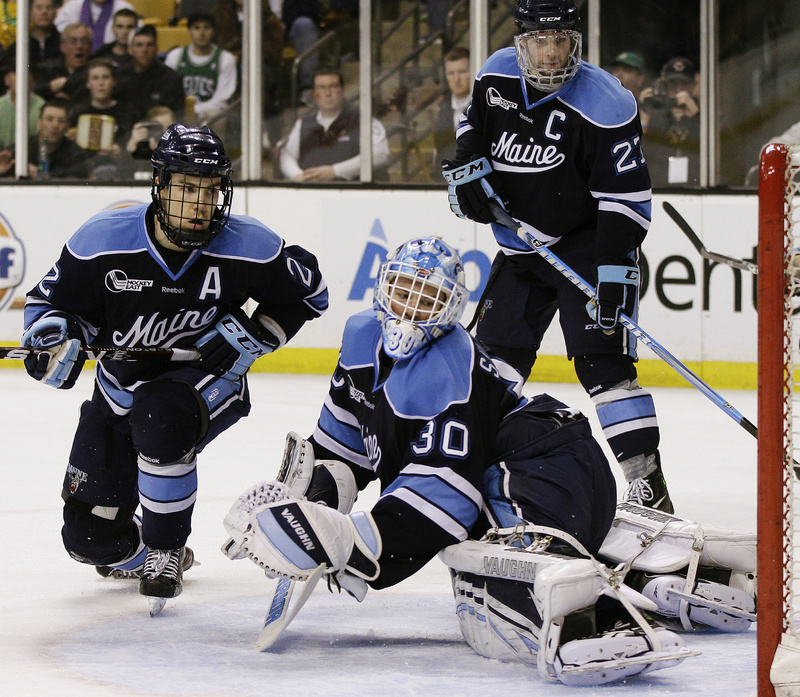 Maine goaltender Dan Sullivan and Stu Higgins, left, watch as a shot by Boston College's Pat Mullane goes into the net for a second-period goal Saturday night during the Hockey East championship game in Boston. Boston College won, 4-1.