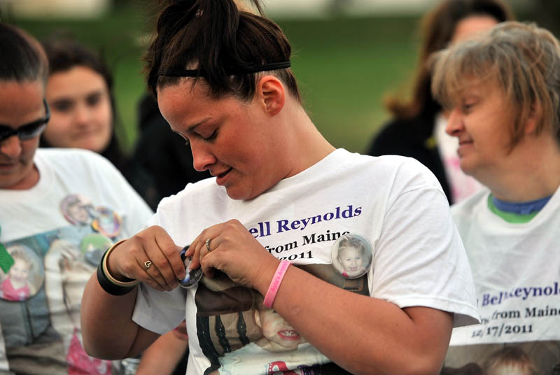VIGIL: Ashley Pouliot, center, pins a button with missing toddler Ayla Reynolds picture on to her Ayla Reynolds t-shirt before a vigil at the Church of God on Upper Main Street in Waterville Thursday.
