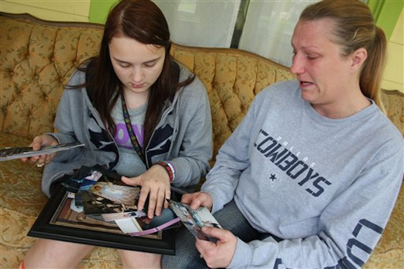 In this photo taken Tuesday, April 17, 2012, Kenneth Weishuhn's sister, Kayla Weishuhn, 16, and his mother, Jeannie Chambers, look at photos of Kenneth, 14, who committed suicide Sunday, April 15, 2012, at their home Primghar, Iowa. Chambers said she knew her son was being harassed but that she and the rest of the family didn't realize the extent of the bullying. (AP Photo/Sioux City Journal, Laura Wehde)