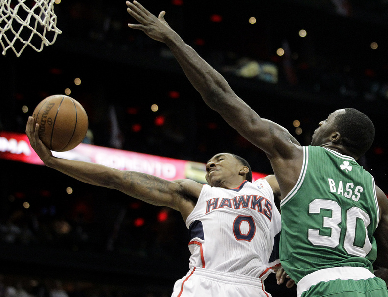 Atlanta Hawks' Jeff Teague, left, puts up a shot past Boston Celtics' Brandon Bass in Game 1 of the opening round of the playoffs Sunday in Atlanta.